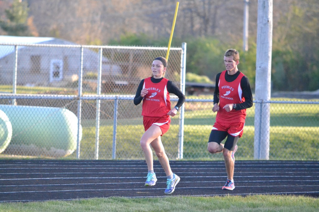 Dominating the distance running events at Tuesday's West Union Invitational were the Peebles brother and sister team of Dan Seas, right, and Jenny Seas, left. Here, the pair compete int he 3200 Meter Run, where both the boys and girls ran at the same time. Dan won the 1600 Meter and 3200 Meter Race, and not to be outdone, sister Jenny did the same in a very successful day. Photo by Mark Carpenter - People's Defender