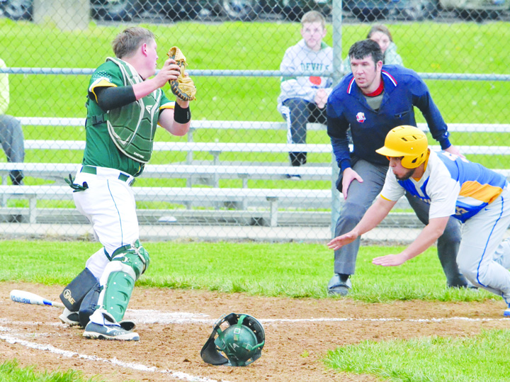 Manchester's Mason Applegate, right, dives headfirst towards home plate as North Adams catcher Kenny Branch waits to make the tag.  Applegate was able to slide under the tag and score the first Greyhound run of the game, though it was the Devils who took the win 7-2.  Home plate umpire Matt Carson looks on to make the call.  Photo by Mark Carpenter