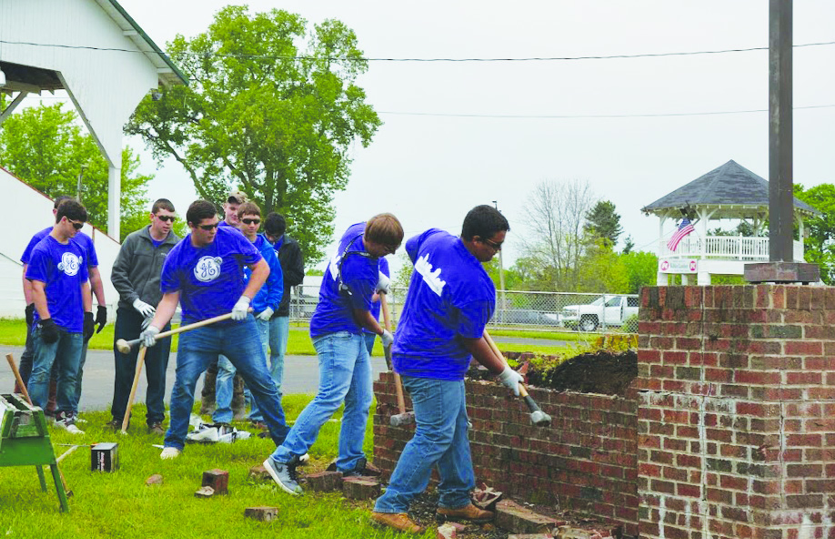 Students working at the Adams County Fairgrounds help demolish a brick structure as part of their Community Day work.