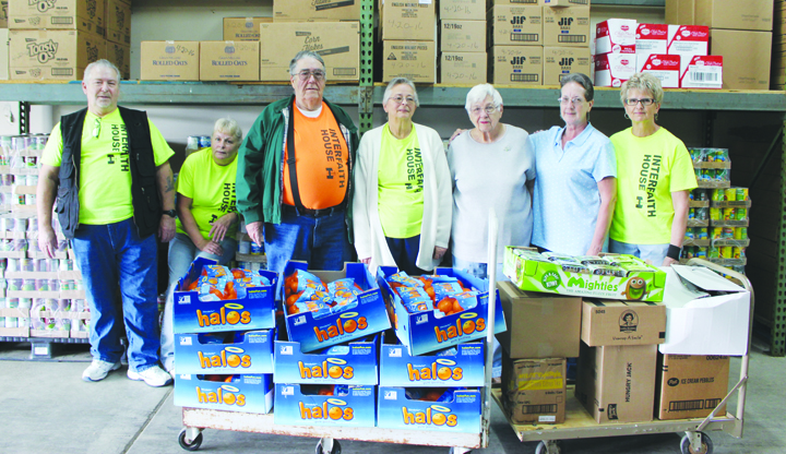 Interfaith House volunteers Robert Zink, Renee Velzkak, Gene Marshall, Carol Marshall, Joe-Ann Weber, Connie Henson, and Judy Robinson are standing behind two skids of groceries donated by New Life Ministries in Hillsboro.
