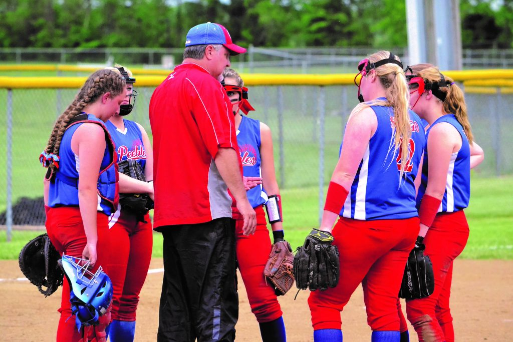 Peebles head coach Doug McFarland meets with his infield during a crucial moment late in the Lady Indians' 8-5 win over Portsmouth Notre Dame on May 12, a win that gave the Peebles girls a sectional title and a trip to the distrcit tournament. Photo by Mark Carpenter.