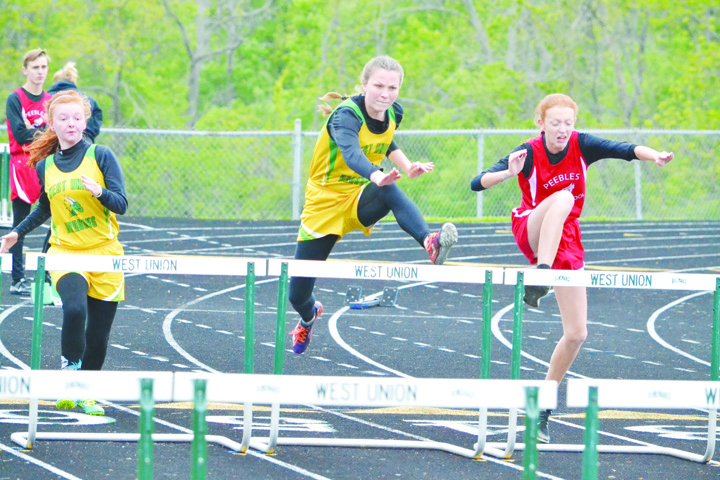 West Union's Rebekah McCarty, center, leads the way on her way to victory in the Girls 100 M Hurldes in last week's Adams County Track Meet.  Photo by Mark Carpenter.