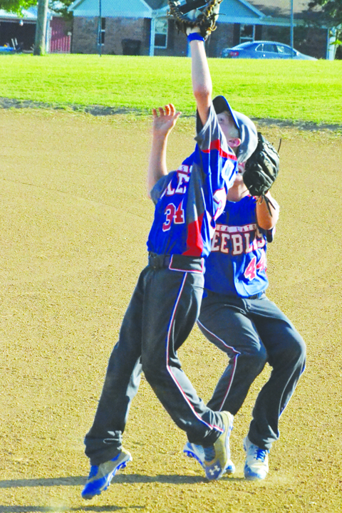 """Peebles first baseman Wyatt Cluxton backs up and grabs this pop-up with back-up help from second baseman Zane Knechtly during action in the """"B"""" league baseball tournament in Peebles on June 28.  The Peebles """"Team Latos"""" squad saw their season end with a 16-6 loss to North Adams."""