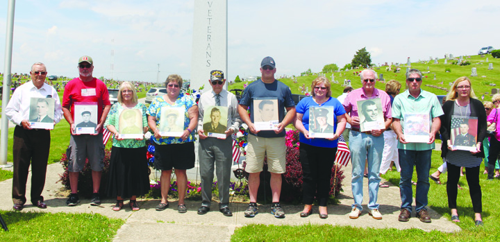 Family and friends pose with photographs of servicemen from Adams County who were killed in action. This photo was taken during services held at the Locust Grove Cemetery.