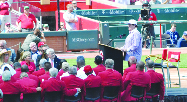 Surrounded by members of the Cincinnati Reds Hall of Fame and other team dignitaries, Pete Rose, right, gives his induction speech as he became the newest member of the Reds HOF during pre-game ceremonies on Saturday, June 25.