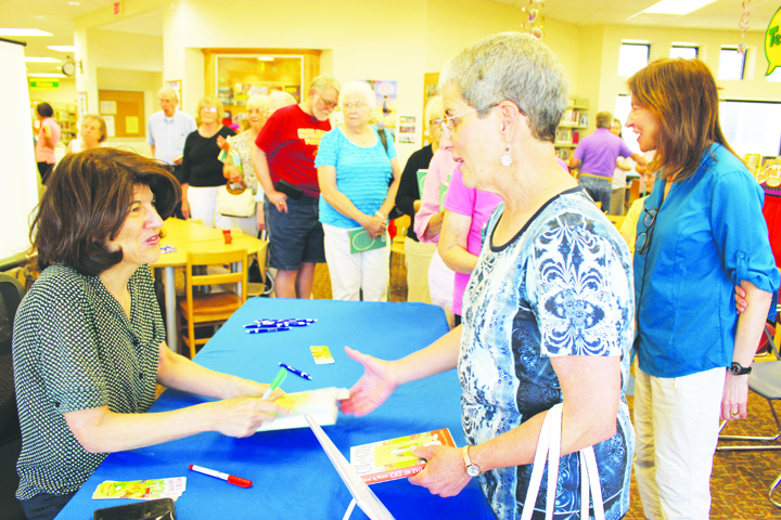 Local author Julie Salamon, left, signs books and greets visitors at the North Adams Library on June 11.