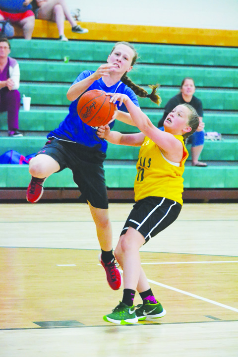 North Adams eighth grader Braylie Jones, right, makes the play on defense, thwarting this Northwest drive to the basket, during action from the June 8 shootout.