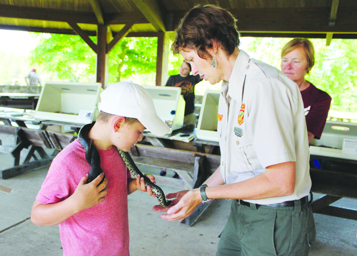Jenny Richards, right, Head Naturalist at the Shawnee State Park Nature Center, allows this young man to get up close and personal with this reptile during the Return of the Snakes program on June 25.
