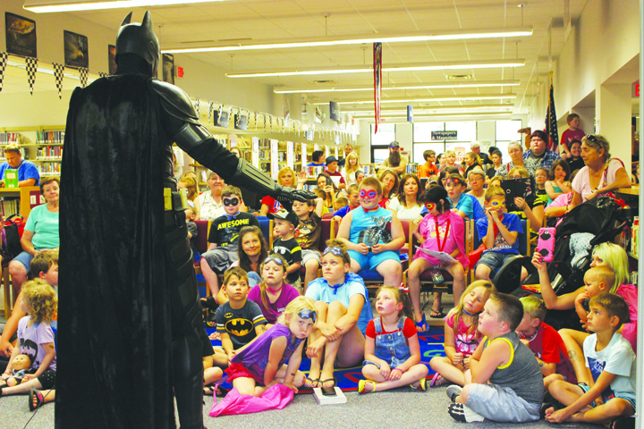 An enraptured audience of youngsters listens intently to the message of the Caped Crusader during his stop at the Peebles Library on July 6.