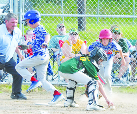 "As North Adams catcher Christopher Young reaches for the loose ball, Peebles' Mason Sims crosses the plate with the first run in the July 7 Class ""C"" Tournament championship game."