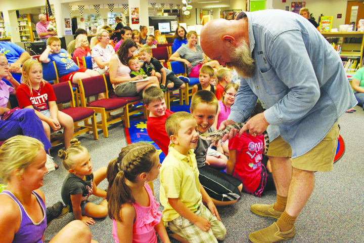 Peter Rushton, Owner of PT Rushton Reptiles, allows a blue-tongued skink to get up and personal with this young man during his presentation at the Peebles Library on July 25.