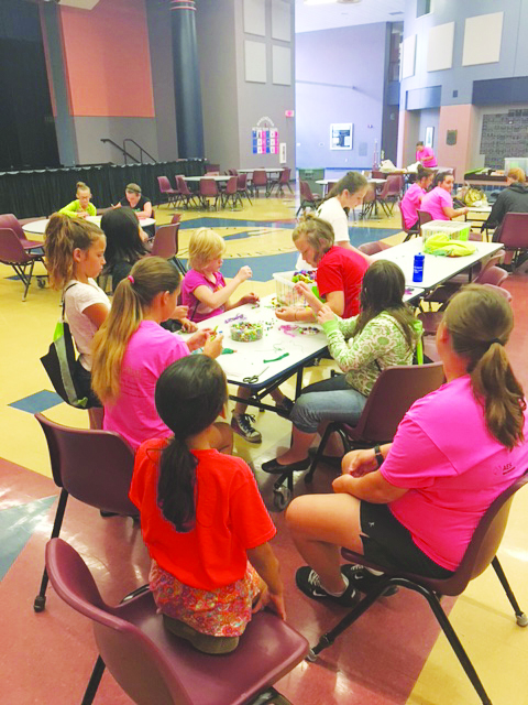Participants in the Summer R.E.C. program work on crafts on a rainy day.