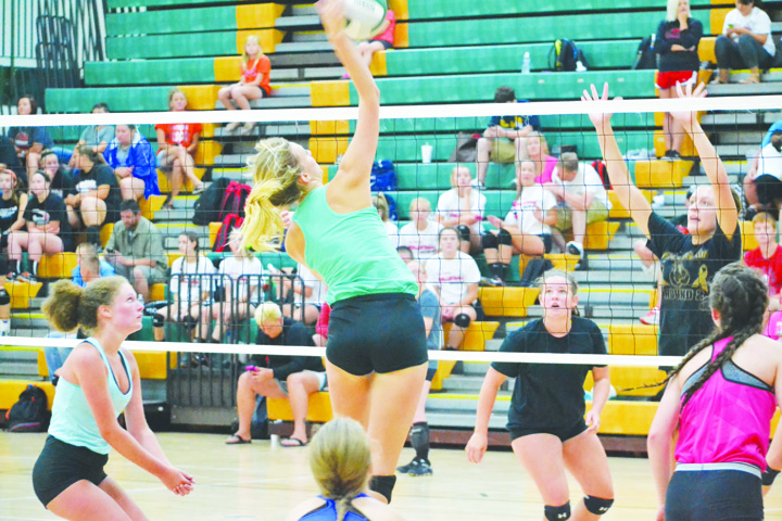 North Adams' Madison Jenkins, with teammates on all sides, goes up for the kill in action from the July 7 tournament held at North Adams High School.