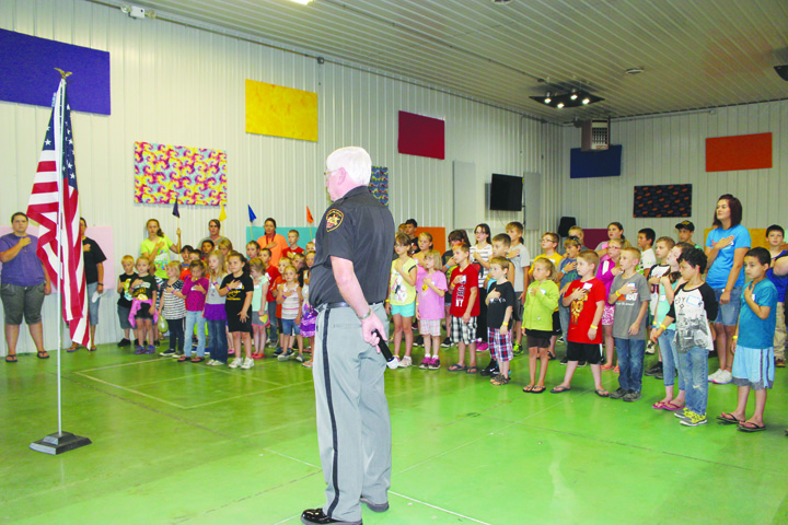 Adams County Sheriff Kimmy Rogers leads his group of Junior Deputy Boot Campers in Seaman in the Pledge of Allegiance.