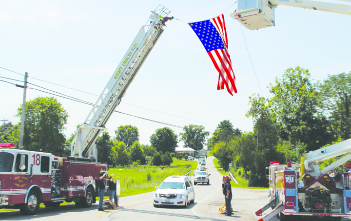 The funeral procession for Franklin Township firefighter Billy Purtee passes under the arch created by West Union and Mt. Orab Fire Departments.