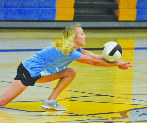 Truly hands-on coaching as new MHS volleyball coach Kaci Compton digs one out while participating in a drill at a volleyball practice last week.