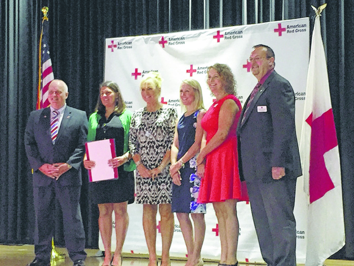 Leeann Puckett of West Union, second from left, receives the Red Cross Wellness Hero Award during ceremonies on Aug. 18.  To the left of Puckett is State Representative Terry Johnson.  Puckett is the current chair of the Adams County Health and Wellness Coalition.