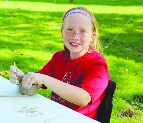 This young lady is all smiles as she creates pottery at the annual Serpent Mound Archaeology Day.
