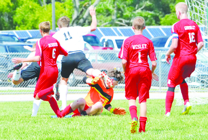In a scramble in front of the net, Peebles goalkeeper Trenton Wheeler takes a cleat to the head from Lynchburg's Damin Pierson in action from last Saturday's SHAC Soccer Preview in Fayetteville.