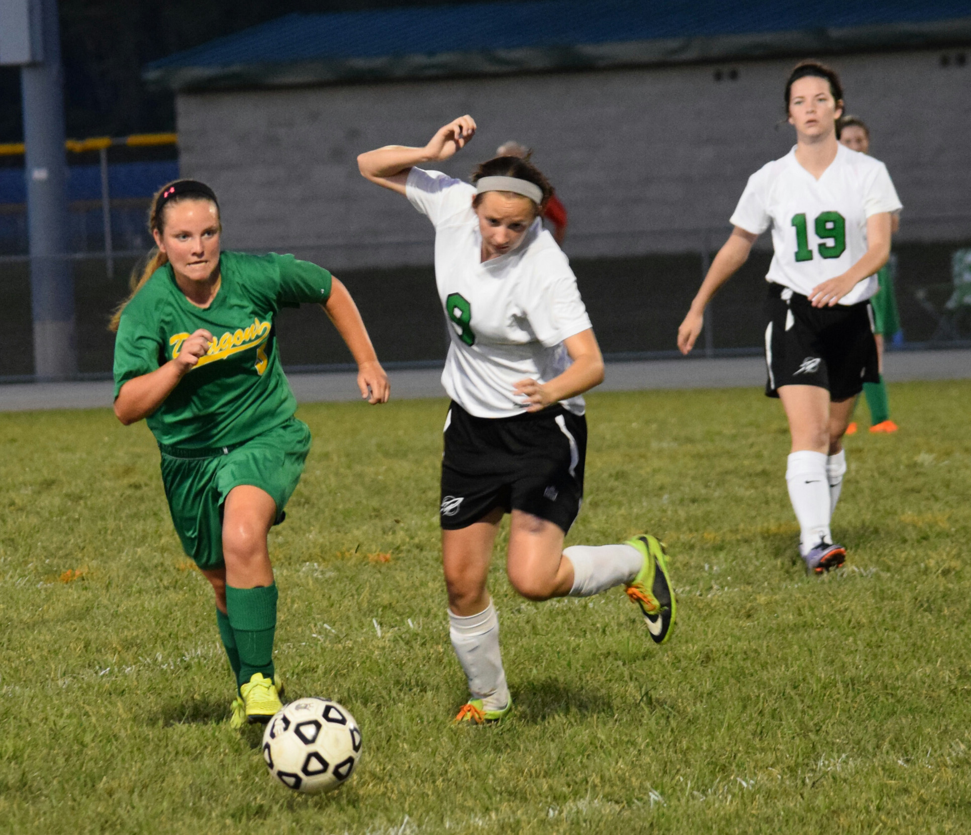 West Union's Shannon Runyan, left,  chases down the ball with Fayetteville players in pursuit during the Lady Dragons' 3-1 win on Monday night.