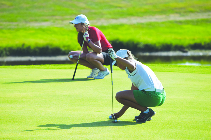 Simultaneously, Peebles' Savannah McCoy, background, and West Union's Alex Clark, foreground, study the ball placement and the greens during play from Round One of the SHAC Girls Golf Tournament last Friday at Hilltop Golf Course.