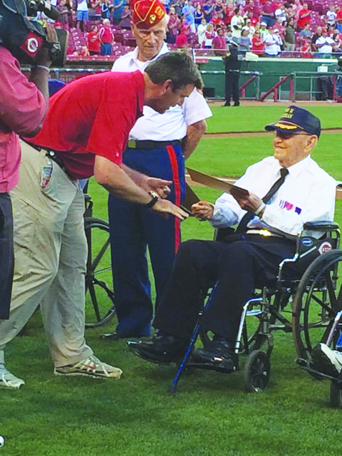 World War II veteran and 96-year old Tom Hughes is awarded a Hometown Hero Certificate for his service by Cincinnati Reds CEO Phil Castellini