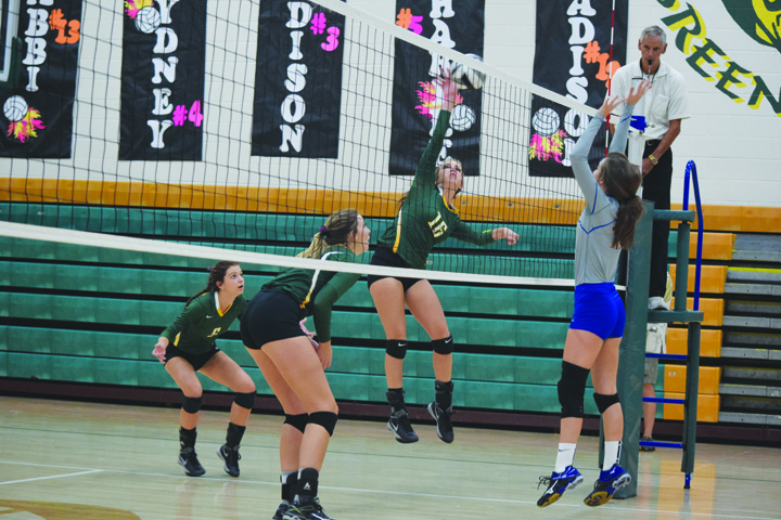 With Manchester's Abby McFarland in position to block, North Adams' Brooklyn Stout goes up for the kill attempt in action from last Tuesday night's match.