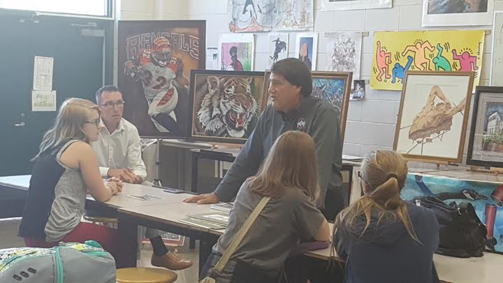 Artist Gary Blevins, center, speaks to a freshman art class at West Union High School on Sept. 21.