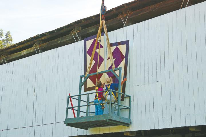 Allen Miller and his son, Marcus, placing the quilt square on Kirker Covered Bridge