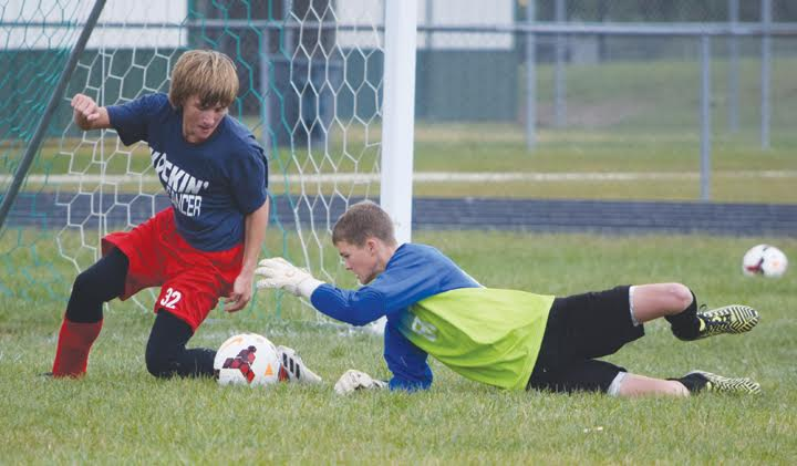 North Adams goalkeeper Cole Wagner reaches out to grab this ball before Peebles' Weston Browning can turn a round and get a shot off in action from Saturday's boys soccer game in Seaman, won by the Green Devils 8-1.