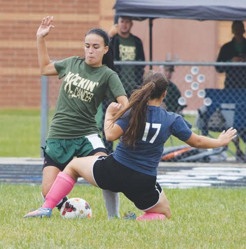 "North Adams senior Kitasha Mesmer battles for possession with Peebles' Kim Kreal (17) during this action from last weekend's ""Kickin Cancer"" event at North Adams High School.  Mesmer scored her first goal of the season to help her team to a 3-1 win over the Lady Indians."