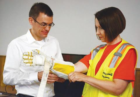 """Kimberly Browning of Peebles, right, is fitted with the NASA RoboGlove, as part of the """"Science of Safety"""" workshops."""