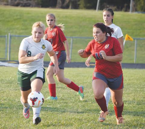North Adams' Jessica Woodall, left, chases the ball upfield with an intense Piketon defender on her heels in action from Tuesday's Div. III sectional final, won by the Lady Devils 6-0.