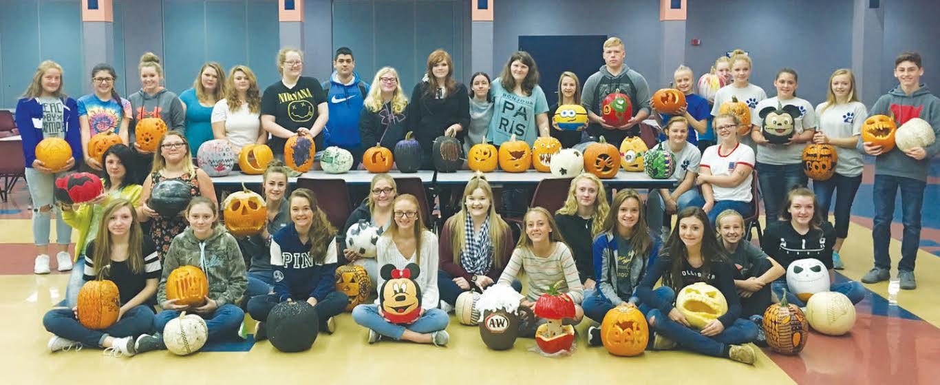 These students creatively represented Manchester Junior and Senior High School by painting and carving pumpkins for Woodland Altars (Southern Ohio's First Lighted Pumpkin Festival).  Students had the option to paint, design, or carve pumpkins. Students painted their pumpkins to look like their favorite cartoon or Disney characters or decorated their pumpkins with a variety of zentangle designs. Other students carved their pumpkins to look like scary monsters, or silhouettes of fairies, cats or various spooky words. Pictured: Front row, from left,  Andrea Parker, Autumn Parker, Abby McFarland, Katie Sandlin, Jade Rust, Xena Crummie, Taylor Young, Taylor Morrison, Billie Kinhalt, Jenna McClanahan, Tori Barlow, Kayden Francis and Madison Young;  Middle row, from left,  Jalyn Thacker, Grace Hackney, Vanessa Francis and Destiny Smith; Back row, from left,  Madison Jones, Madison Payne, Mackenzie Leadingham, Ashley Francis, Taylor Hanshaw, Ariann Alexander, Frank Santoriello, Taylor Ogden, Breanna O'Connell, Syliva Jernigan, Melanie Lawerence, Alyssa Grooms, Jacob Calvert, Jasmine Stanfield, Katelynn Swearingen, Gabby Baldwin, Brittany Francis, Sierra Shelton, and Nathaniel Peterson.