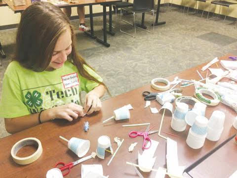 4-H Tech Wizards Madison Bayless, Winchester, engineers a harvester to be powered by Hex Bugs at the Scioto County Ag Bot Challenge Maker station.