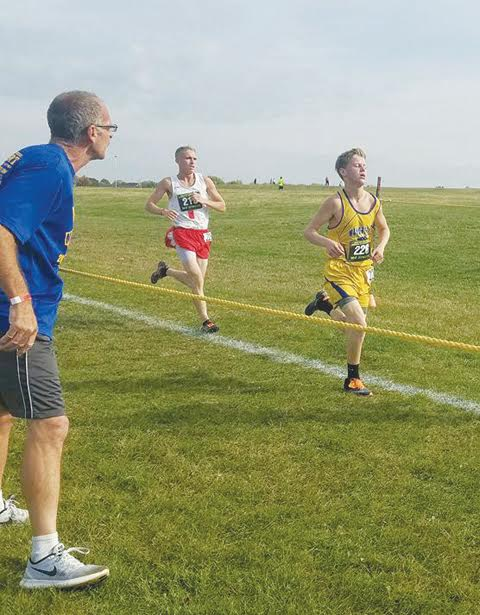 Manchester junior Ethan Pennywitt, right, cheered on by father Lonnie Bilyeu,  will become the first Greyhound in the school's history to compete in the state cross-country meet this Saturday at National Trail Raceway.