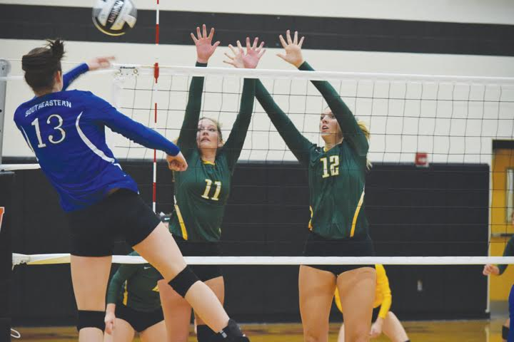 North Adams' Abby Campton (11) and Madison Jenkins (12) go over the net to try and block this return from Southeastern's Ella Skeens during the Oct. 25 Division III district semi-final match in Waverly.