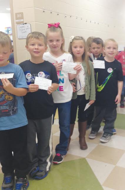 Pictured here are kindergarten students from Mrs. Karisa Miller's kindergarten class.  These students had just voted and are showing their identification card and voter sticker.