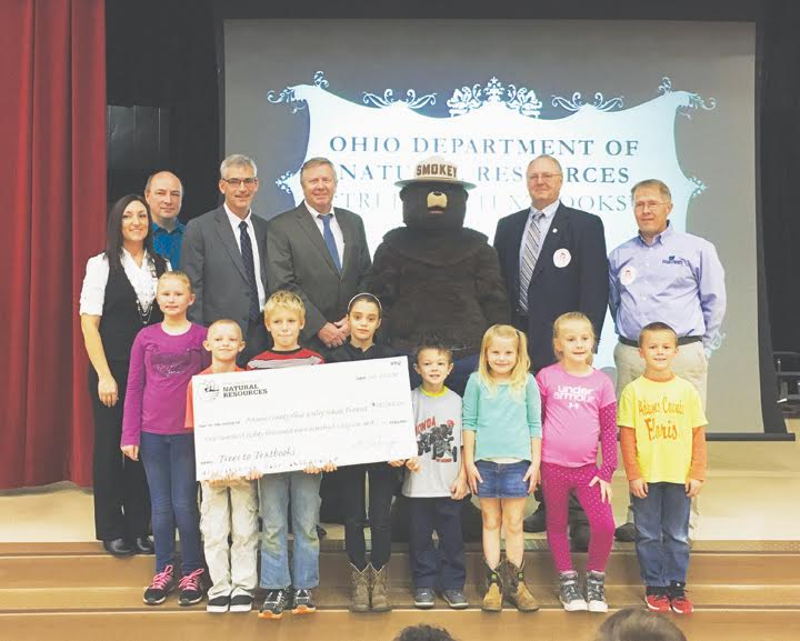 The Ohio Department of Natural Resources (ODNR) awarded more than $2 million to 16 rural Ohio school districts after selling timber from state forests as part of the Trees to Textbooks program. The Adams County Ohio Valley School District in Adams County received a check recently for $180,966 from Trees to Textbooks at Peebles Elementary School in Peebles. Pictured Back row,from left are: Amanda Lamb, Principal of Peebles Elementary School; John Lewis, Richard Seas, Superintendent of the Adams County Ohio Valley School District, James Zehringer, Director of ODNR, Robert Boyles, Ohio's State Forester, and Dale Egbert, Manager of Shawnee State Forest. Peebles Elementary School students are pictured holding the check. Front row, from left, Tatum Rigdon, Damon Holt, Steven Merrick, Chloe Taylor, Crew Wilson, Gabrielle Howard, Kendall Myers and Calen Vogler.