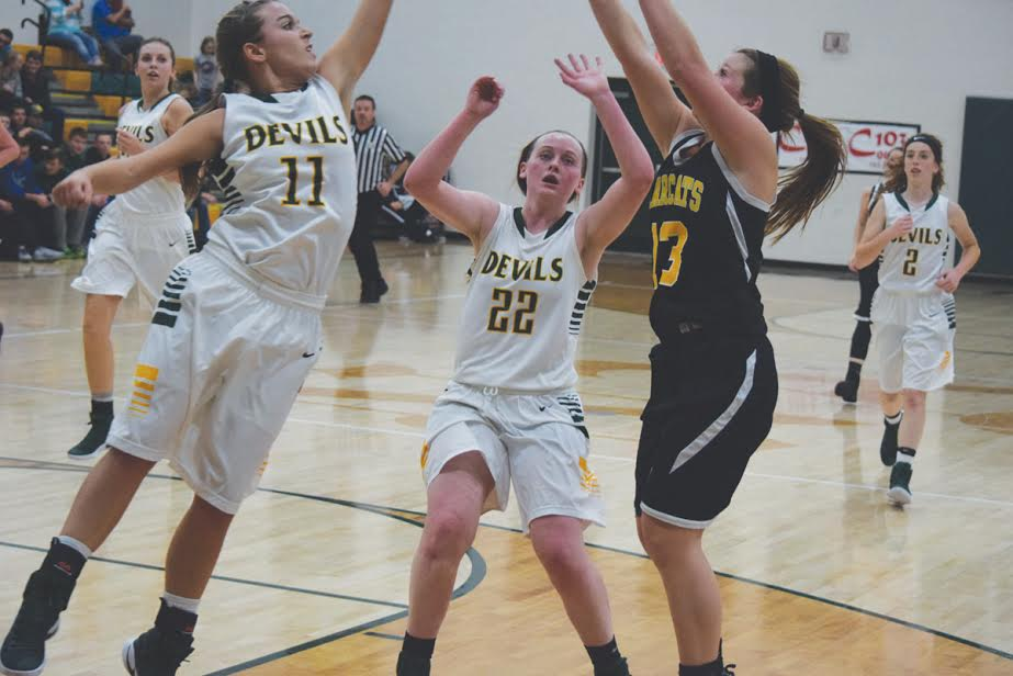 North Adams' Lakyn Hupp (11) and Grace McDowell (22) converge on a Paint Valley shooter in action from Tuesday night's varsity contest. Hupp and McDowell combined for 32 points as the Lady Devils won their season opener by a final score of 56-32