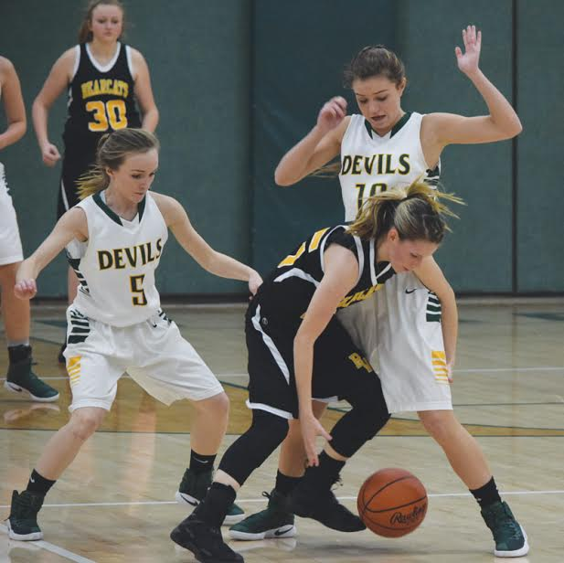 Maddie Toole (5) and Charlee Louden (10) put the always present North Adams defensive trap on this Paint Valley ballhandler in action from Tuesday night's Lady Devils' win.
