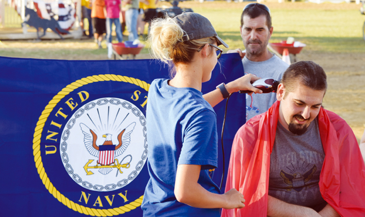 Kelsey Friend, left, was one of the audience members who had her name drawn to help shave the head of Navy-bound George Hesler in a ceremony held on Saturday night of the Adams County Fair.