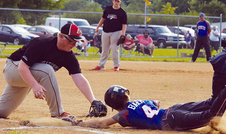 Losing his helmet, Peebles' Brennan Barr slides safely back into first base on a pickoff attempt in the first inning of the 14U tournament title game on July 3.