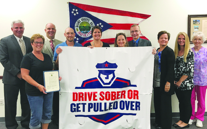 Members of the Adams County Safe Communities Coalition receive the Drive Sober or Get Pulled Over 2017 proclamation from the Adams County Commissioners, declaring their support for the Drive Sober or Get Pulled Over 2017 Labor Day Holiday Statewide Crackdown.   Pictured above, left to right, are: Ty R. Pell, Adams County Commissioner, Debbie Ryan, Adams County Safe Communities Coordinator, Brian Baldridge, Adams County Commissioner, Jason Work, Adams County Health Department, Leeann Puckett, GE-Peebles and Adams County Health and Wellness Coalition, Holly Johnson, Adams County Economic and Community Development Director, Dr. William Hablitzel, Adams County Health Commissioner, Diane Ward, Adams County Commissioner, Amanda Fraley, Adams County Economic and Community Development Office, and Beverly Mathias, Adams County Health Department.