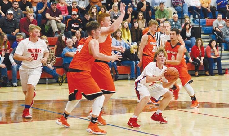 Peebles point guard Weston Browning looks for an open teammate as he is swarmed in the lane by Whiteoak defenders.  Browning scored 12 points in the Indians' 65-50 win last Friday night.