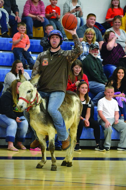 Michael Mills from the Adams County Sheriff's Department team gets off a one-handed shot attempt during the Donkey Basketball event last weekend at Manchester High School.