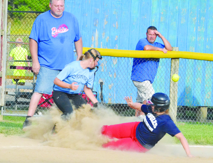 Peebles' Hope Brown slides safely into third base as the ball eludes the Manchester third baseman in action from last week's semi-final softball tournament game in Hillsboro, won by the Lady Indians 6-0.